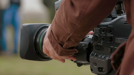 Cameraman filming outdoors. Close-up