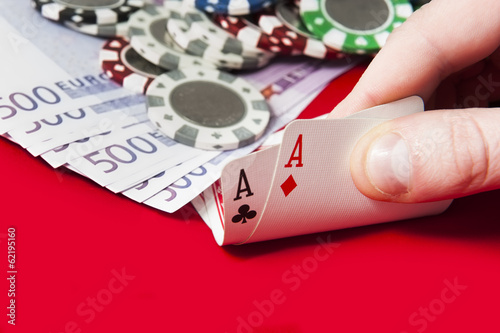 Man holding par of aces in front of poker chips and euro bills