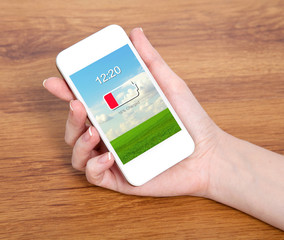 woman hand holding a touch white phone with low battery on a scr