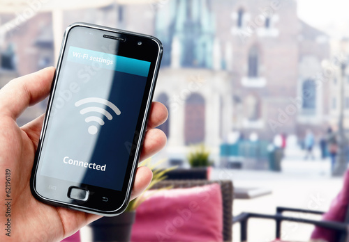 canvas print picture Hand holding smartphone with wi-fi connection in cafe