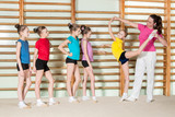 Gymnastics coach teaching little girls