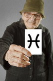Elderly woman holding card with printed horoscope Pisces sign.