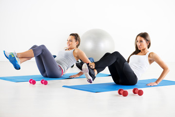 Beautiful Fitness girls doing abs exercise.