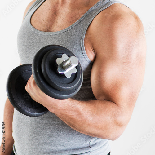 Young man lifting the weights with biceps exercise.