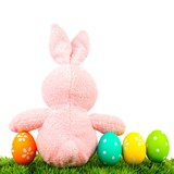 Pink toy Easter bunny on grass with colorful eggs