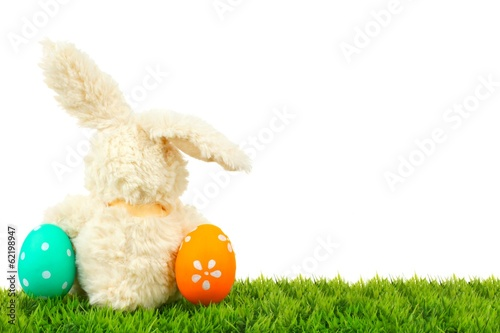 Toy Easter bunny on grass with colorful eggs