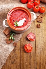 Tasty tomato soup on wooden table