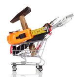 Construction tools in shopping cart isolated on white