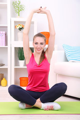 Young beautiful fitness girl exercising  at home