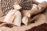 Sacks with coffee beans on wooden table, on sackcloth
