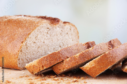 Sliced bread on wooden board on bright background