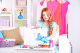 Young girl fashion designer sews new dress in workroom