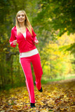Woman running in autumn forest.  Female runner training.