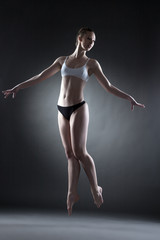 Studio shot of graceful dancer posing in jump