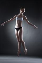 Studio shot of graceful dancer posing in jump