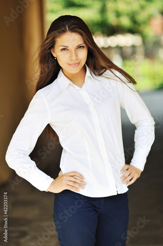 Outdoors street portrait of beautiful young brunette smiling tee