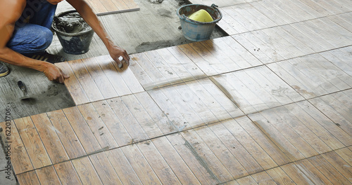 Construction worker tiling the floor