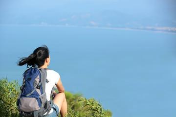 woman hiker enjoy the view at seaside mountain peak