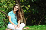 Attractive girl in glasses sitting in a park