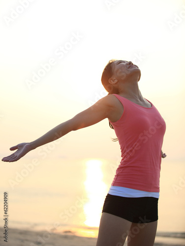 cheering woman hiker open arms at sunrise/sunset  seaside