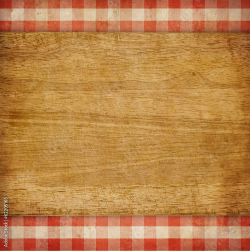 Cutting board over red grunge checked gingham picnic tablecloth
