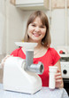 woman with electric sausage meat mincer
