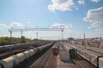 Many long passenger and freight trains at railway station