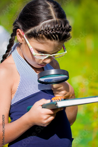 girl looking through magnifying glass on beetle