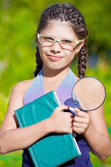 Girl with magnifying glass and book