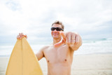 Smiling man with surfboard at beach pointing with finger