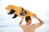 Man resting surfboard on head at beach