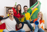 Multi ethnic group of people cheering football match