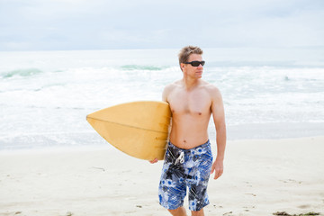 Serious looking man walking with surfboard at beach