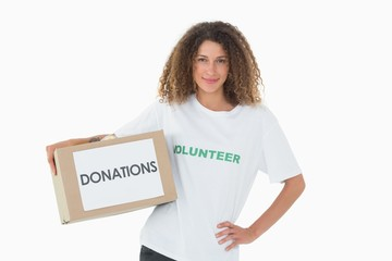 Happy volunteer holding a box of donations with hand on hip