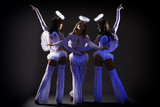 Trio of sexy female dancers posing under UV light