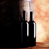 red wine bottles and barrel