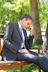Sad businessman in park