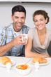 Smiling couple sitting having breakfast together