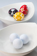 White ceramics bowls, golf balls and eggs