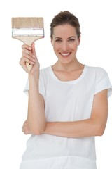 Portrait of a smiling woman with paintbrush