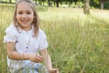 Smiling relaxed young girl sitting in field
