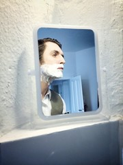 man shaving with mirror