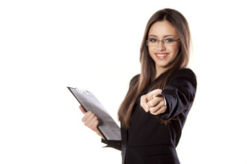 smiling young businesswoman with clipboard pointing at you