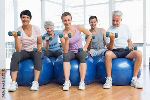 canvas print picture Fitness class with dumbbells sitting on exercise balls