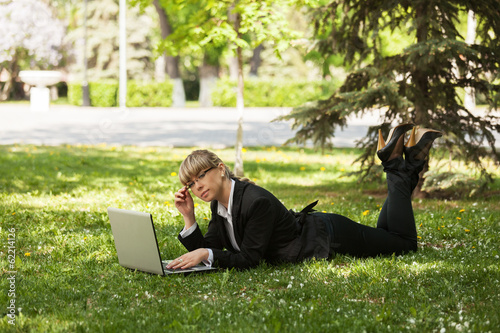 Happy business woman using laptop in a city park