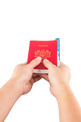Female hand holding Malaysian passport and boarding pass .