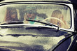 Young people driving retro car in the rain