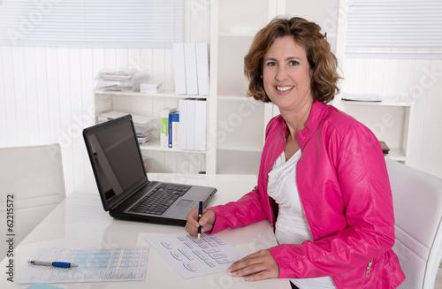 Lachende Angestellte in Pink sitzend im Büro