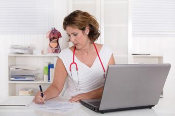 Ärztin sitzend im Büro mit Computer