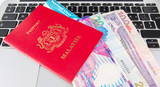 Passport with Hong Kong dollars and laptop